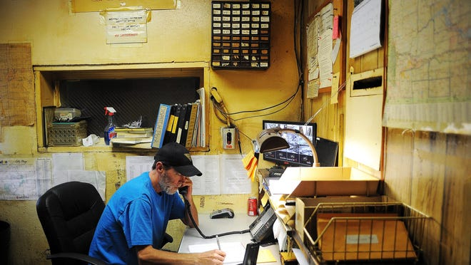 Mike Terry, a dispatcher with Yellow Cab, talks to a customer over the phone on Thursday, Aug. 27, 2015, at the Yellow Cab office in Sioux Falls.