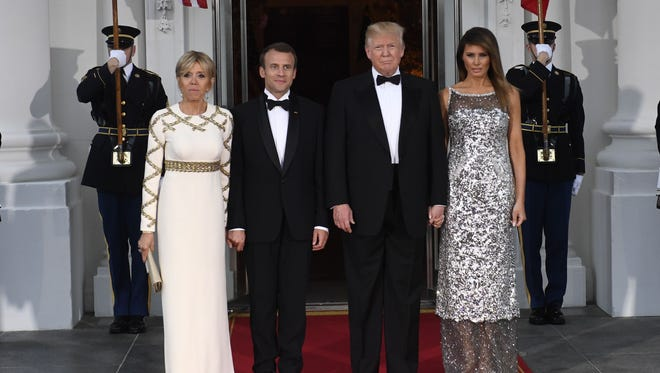 President Trump and first lady Melania Trump welcome French President Emmanuel Macron and his wife, Brigitte Macron, as they arrive for a State Dinner at the North Portico of the White House in Washington.
