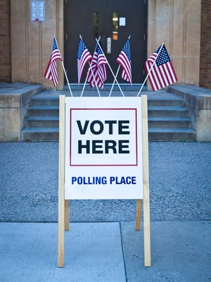 """""""Vote Here"""" sign outside the entrance of a polling place building"""