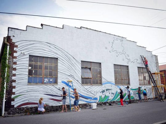 Artists work on the facade of Waldo's on Stratton, a Gettysburg art co-op that closed its doors in September. The group, which is starting a fundraising campaign April 17, hopes to reopen in a new location by mid-summer.