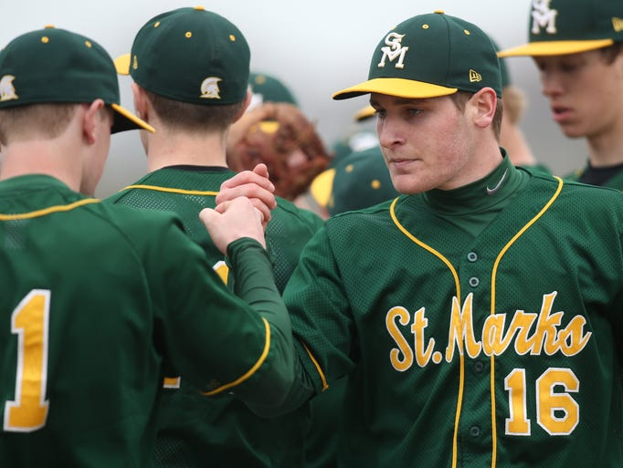St. Mark's starter Tommy Spagnolo (right) greets teammates after throwing a scoreless inning during the Spartans' 4-1 win against Hodgson at home, Friday, March 28, 2014.