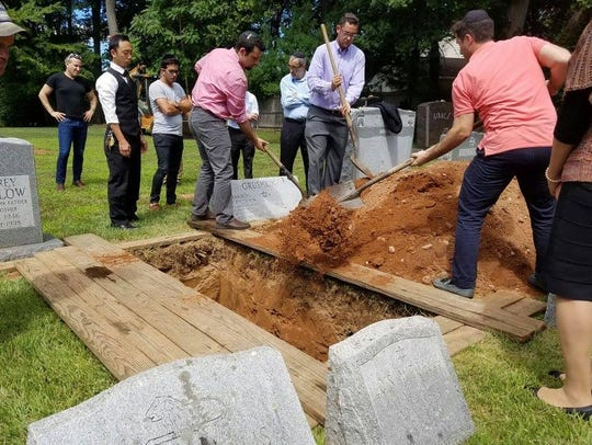 Mourners help fill the grave at the funeral service