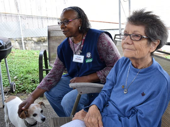 Senior Companion Ella Neal pets her client Mary's helper dog during a visit Tuesday, Nov. 7, 2017. Mary is deaf and has dementia. Both women will benefit from the Empty Stocking Fund this year; Neal will receive a food basket, and Mary a hot, delivered meal.