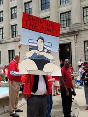 A man holds up a poster depicting Gov. Chris Christie at a rally organized by the Communications Workers of America outside the Statehouse on Thursday, July 13, 2017.