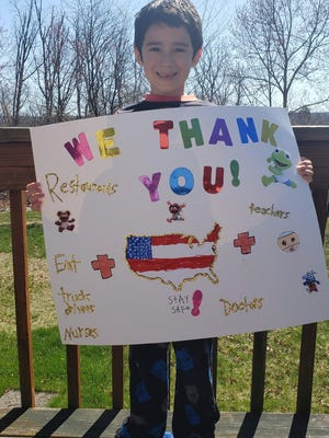 Jayden S., a student at Bushkill Elementary, holds up his sign thanking essential workers.