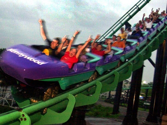 Amusement park visitors ride the Phantom's Revenge