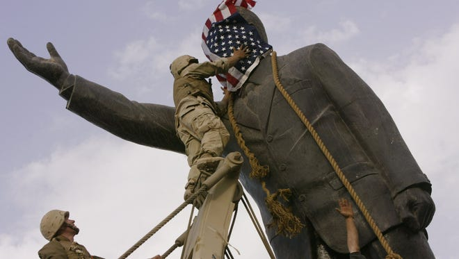 Marines cover the face of a statue of Saddam Hussein with an American flag before toppling it in downtown in Baghdad, in 2003.