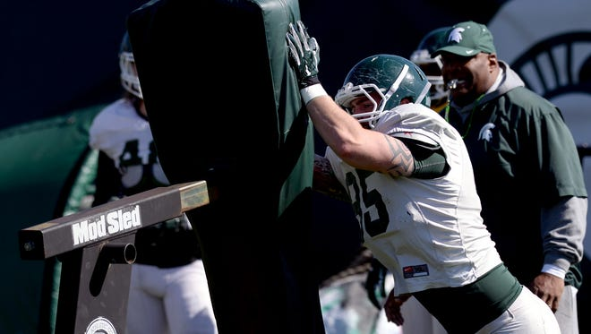 Defensive end Evan Jones (85) goes through drills as defensive line coach Ron Burton looks on as the Spartan football team practices Tuesday, April 6, 2016, at the  John and Becky Duffey Football Practice Fields on the campus of Michigan State University.