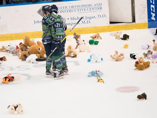 Brendan O'Donnell (21) of the Florida Everblades celebrates with teammate Michael Kirkpatrick after scoring the teams first goal, cueing the annual Teddy Bear Toss during the game against the Elmira Jackals at Germain Arena in Estero Saturday night, December 10, 2016.