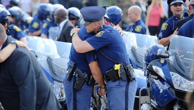 Police officers embrace after the funeral for Trooper Chad Wolf at Fenton High School in Fenton.
