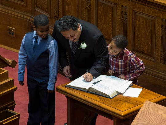 Wisconsin Rep. Leon Young (D-Milwaukee) signs the official