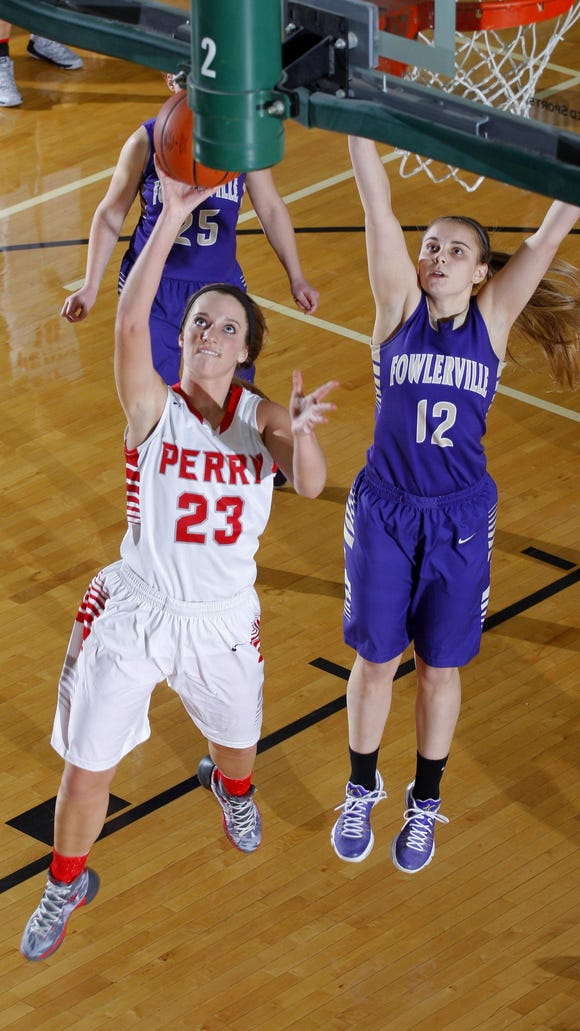 Perry's Kelsey Finch (23) puts up a fast-break layup in front of Fowlerville's Taylor Patterson (12) Wednesday at Williamston High School. Perry won 57-46.