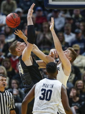 Butler Bulldogs forward Joey Brunk (50) is called for a foul while defending against Purdue Boilermakers center Isaac Haas (44) during the Crossroads Classic at Bankers Life Fieldhouse in Indianapolis on Saturday, Dec. 16, 2017.
