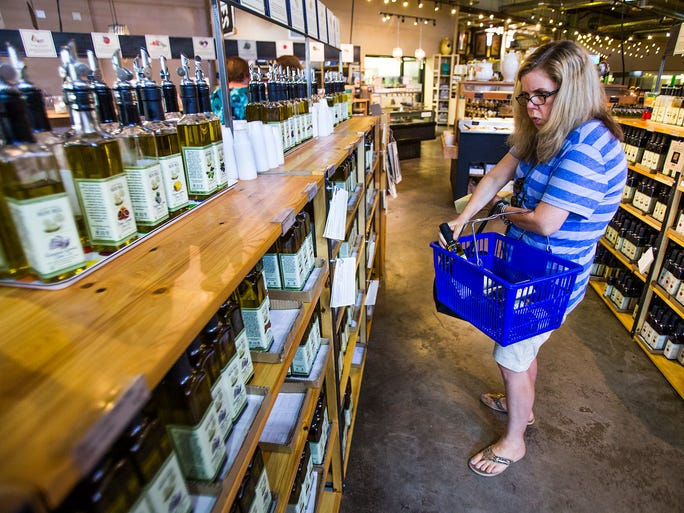 Tracy Friess, a visitor from Virginia Beach, Va., shops for olive oil at the Queen Creek Olive Mill.
