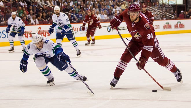 Coyotes defenseman Klas Dahlbeck takes a shot over Canucks right wing Radim Vrbata in the first period at a Coyotes home game March 22, 2015 at Gila River Arena in Glendale, Arizona.