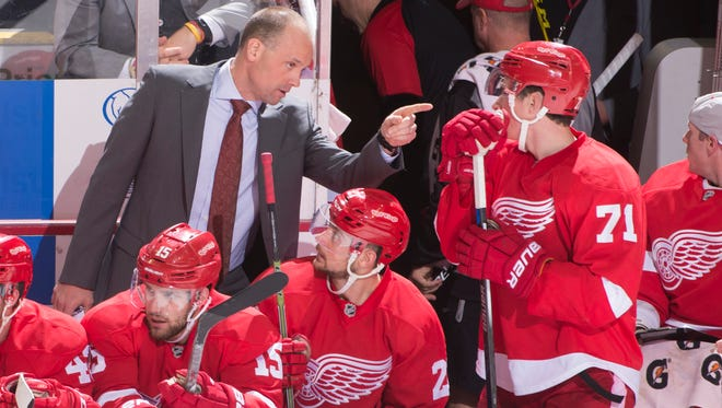Red Wings head coach Jeff Blashill talks to rookie center Dylan Larkin (71) in the second period Tuesday night in Detroit.