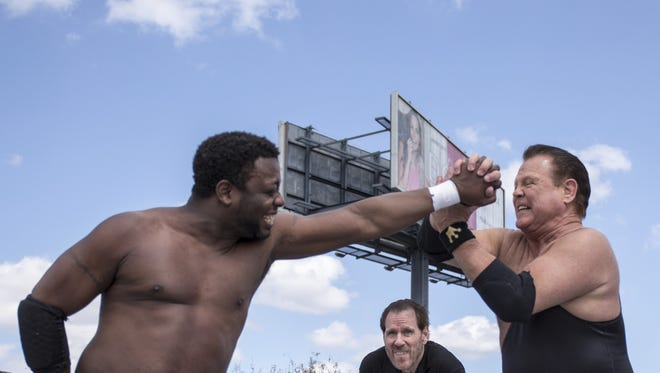 """Jerry """"The King"""" Lawler, right, and Derrick King wrestle at the grand opening of King Jerry Lawler's Memphis BBQ Company."""