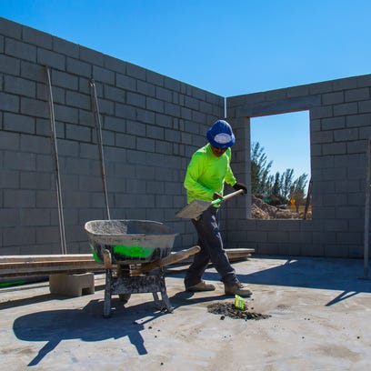 A worker for Naples Concrete and Masonry clears debris