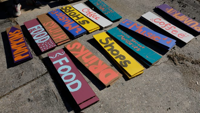 Signs pointing to amenities are ready to be hung during Better Block McKinley, a one-day transformation of McKinley Street into a two-way pedestrian friendly street in Freetown Oct. 22, 2016, in Lafayette.