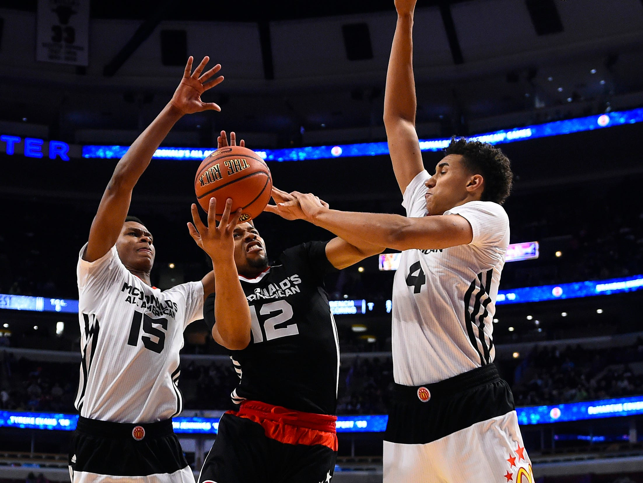 Apr 1, 2015; Chicago, IL, USA; McDonald's All American East guard Isaiah Briscoe (12) shoots the ball against McDonald's All American West guard PJ Dozier (15) and center Chase Jeter (4) during the first half at the United Center. Mandatory Credit: Mike DiNovo-USA TODAY Sports