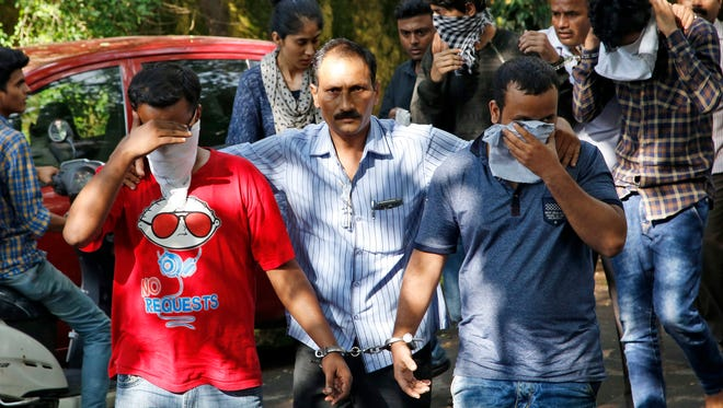 A police official, center, escorts two men outside the court in Thane, outskirts of Mumbai, India, Thursday, Oct. 6, 2016. Indian police have arrested 70 people and are questioning hundreds more after uncovering a massive scam to cheat thousands of Americans out of millions of dollars by posing as U.S. tax authorities and demanding unpaid taxes.