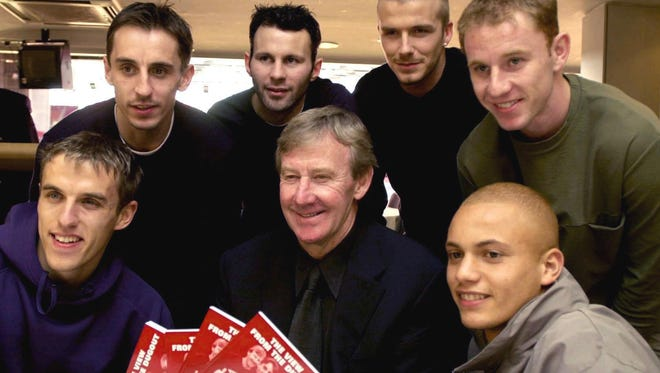 """In this March 1, 2001 file photo, Eric Harrison, center, poses for a photo with Manchester United players from left, Gary Neville, Phil Neville, Ryan Giggs, David Beckham, Nicky Butt and Wes Brown during his book launch, at Old Trafford, in Manchester, England. Harrison, the Manchester United youth team manager who launched the career of David Beckham as part of the renowned group of """"Class of 92"""" players, has died."""