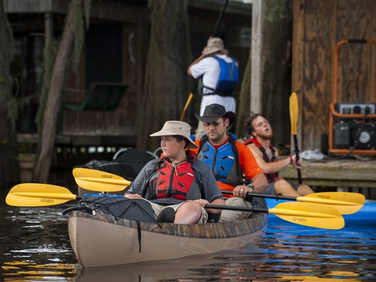 Martin Everett, 13, and his father Christopher prepare to depart from the houseboats to begin their second day of the BSA Swamp Base program in the Atchafalaya River Basin near Henderson, LA, Tuesday, July 1, 2014. The program is a 60-mile kayak trek through the basin area and is held by the Evangline Area Council of the Boy Scouts of America.