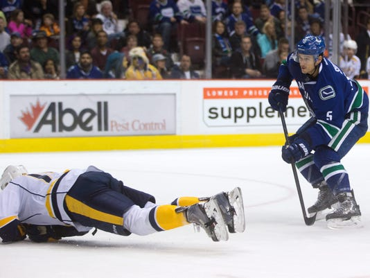 Nashville Predators' Mattias Ekholm, left, of Sweden, blocks a shot by Vancouver Canucks' Luca Sbisa, of Switzerland, during the first period of an NHL hockey game in Vancouver, British Columbia, on Sunday, Nov. 2, 2014. (AP Photo/The Canadian Press, Darryl Dyck)