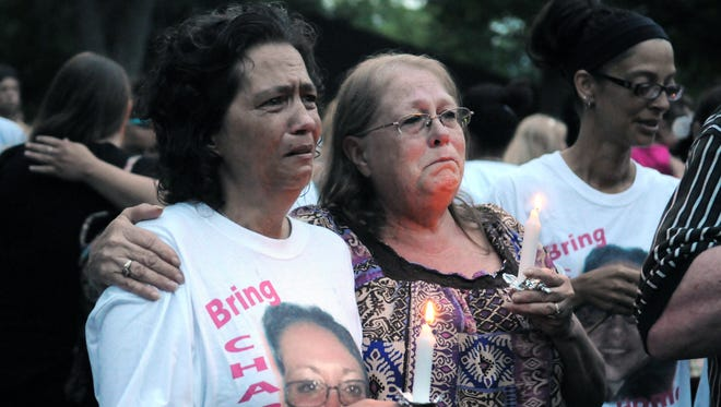 Lynnette Mitchell, right, hugs Angie Robinson, mother of Tameka Lynch, during an early June 2014 candlelight vigil at Yoctangee Park in Chillicothe, Ohio.