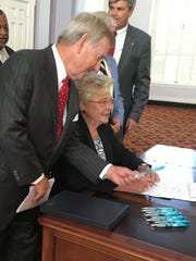Montgomery Mayor Todd Strange hands a pen to Gov. Kay Ivey as she prepares to sign the Alabama Jobs Act on Thursday at the Capitol.