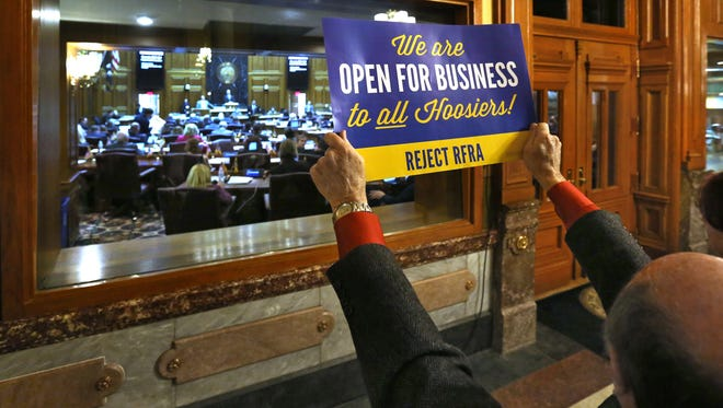 A protester holds up a sign opposing SB 101, the Religious Freedom Restoration Act, outside the House chamber as representatives debate March 23, 2015.