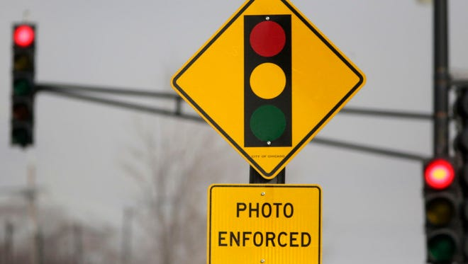 A sign warns motorists of the presence of a red light camera in Chicago. Mayor Rahm Emanuel's administration on March 8, 2015, announced 50 controversial red-light cameras will be taken down from about two dozen locations citywide.