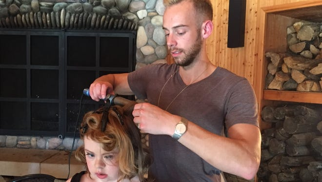 Stryker Ostafew styles Amber Coia's hair before she model in Thursday's EveryMaya fashion show.