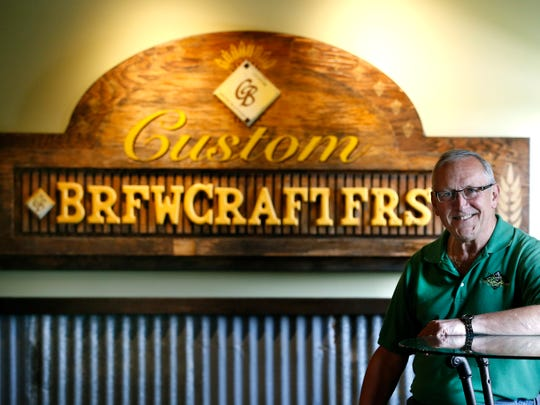 Mike Alcorn, owner of CB Craft Brewers, sits in front of the original sign for his Honeoye Falls craft brewery.
