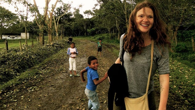 Kristin Van Busum, founder and director of Project Alianza, walks with the children of coffee farm workers.