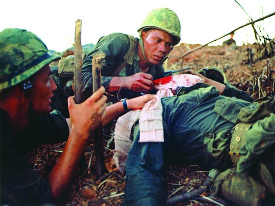 Navy corpsman David Lewis Boucher, 22, Shelbyville, Tenn., (left) and Marine Staff Sgt. Ruben Santos treat Pvt. William Vizzerra, 21, Phoenix, Ariz., near the crest of Hill 881 N. The Hill was one of several strategically important hills surrounded Khe Sahn in western Quang Tri Province in Vietnam's I Corps. The fighting between the Marines and North Vietnamese Army (NVA) regulars took place on April 30, 1967.