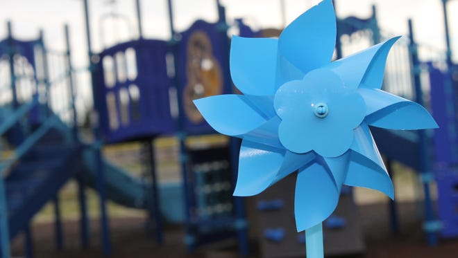 Blue pinwheels, a symbolic reminder of Ty Clements, were given to the crowd at the MILA Elementary playground dedication Tuesday morning.