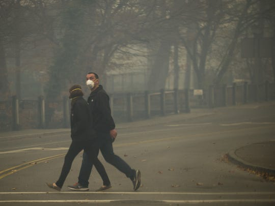 People wearing face masks walk down the Parkway in downtown Gatlinburg Nov. 28, 2016. Thick smoke from area forest fires covered much of Gatlinburg and the surrounding areas.