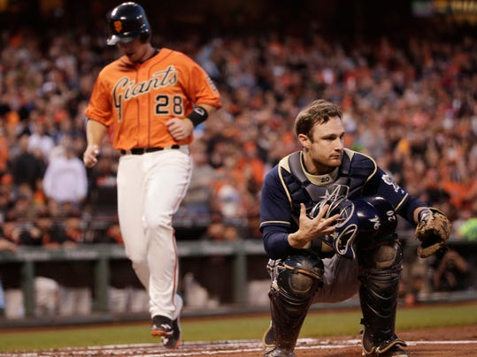 Milwaukee Brewers catcher Jonathan Lucroy, right, catches a wide throw from the outfield as San Francisco Giants' Buster Posey, left, scores on a single by Pablo Sandoval during the first inning of a baseball game on Friday, Aug. 29, 2014, in San Francisco. (AP Photo/Marcio Jose Sanchez)