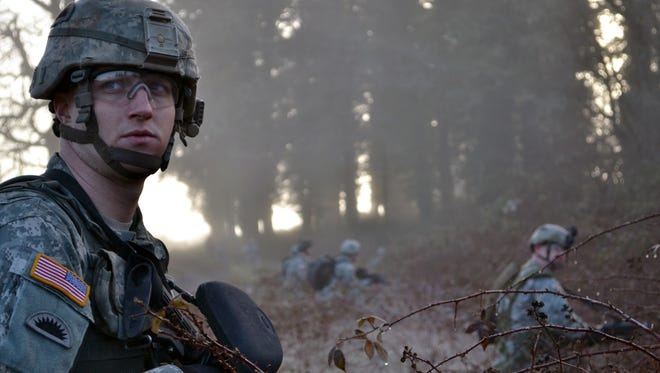 Cpl. Andrew J. Miller, with Bravo Company, 1st Battalion, 186th Infantry Regiment, provides roadside security in the blackberry bushes as the sun rises through the trees during a training exercise March 9 at Fairview Training Center in Salem. (Photo by Spc. Erin J. Quirke, 115th Mobile Public Affairs Detachment)