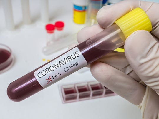 "Gloved hand holding vial of blood. A label on the vial reads ""Coronavirus"" and a box next to ""Pos."" is checked off."