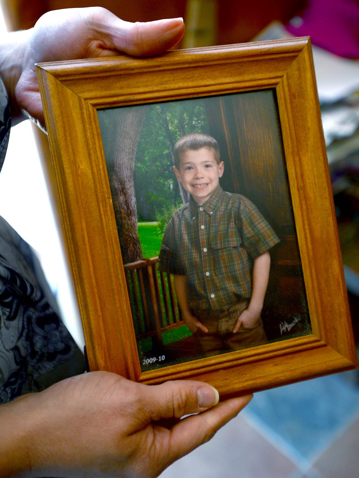 Tiffany Kyle holds a photo of her son, Matthew, taken