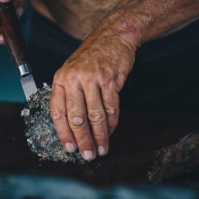 A man opens an oyster