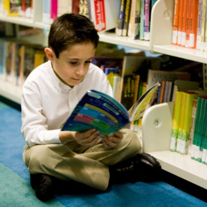 Schoolboy sitting on carpet and reading a book in the