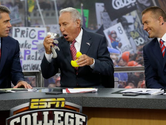 """FILE - In this Oct. 12, 2013, file photo, ESPN College GameDay host Lee Corso, center, talks to mascots from the Washington Huskies and the Oregon Ducks as he makes his prediction of an Oregon win over Washington in an NCAA college football game during College GameDay's broadcast from Red Square on the University of Washington campus in Seattle. At left is co-host Chris Fowler, and at right is co-host Kirk Herbstreit. ESPN's """"College GameDay"""" will broadcast from Times Square on Sept. 23, the first time the popular pregame road show travels to New York City.  (AP Photo/Ted S. Warren, File)"""