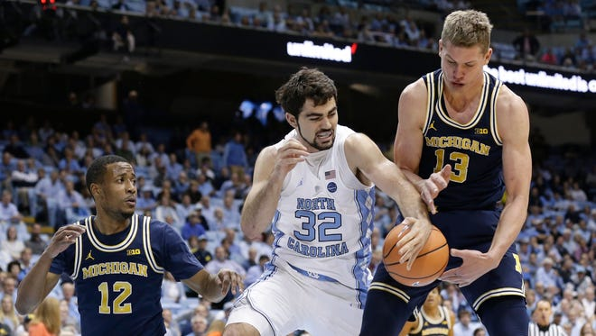 North Carolina's Luke Maye (32) struggles for possession of the ball with Michigan's Muhammad-Ali Abdur-Rahkman (12) and Moritz Wagner (13) during the first half on Wednesday, Nov. 29, 2017, in Chapel Hill, N.C.