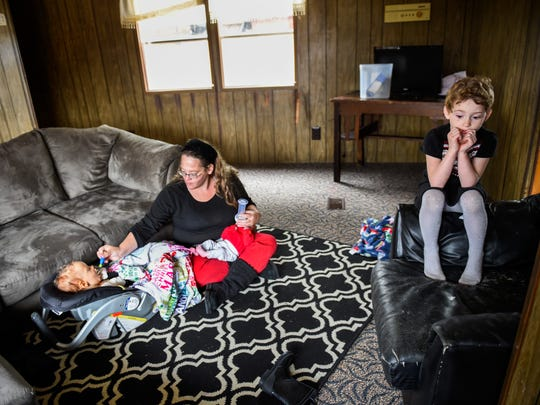 Jennifer Terrill feeds her 16-month-old daughter Kaitlin Estep and 7-week-old Bella Estep at the some time as Abigayle Estep, 6,  waits to play on Sunday, Dec. 4, 2016, in Johnson City, Tenn.