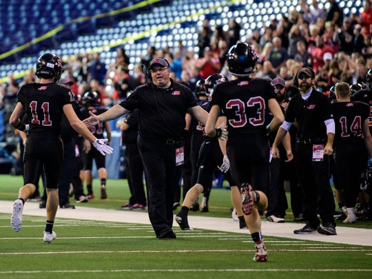 Southridge Head Coach Scott Buening (center) high-fives his team during the first quarter of the IHSAA Class 2A State Championship at Lucas Oil Stadium in Indianapolis, Ind., Saturday, Nov. 25, 2017.