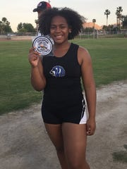 Maijoy Wooten holds up her first-place patch after taking first place at the Division 3 prelims on Saturday.