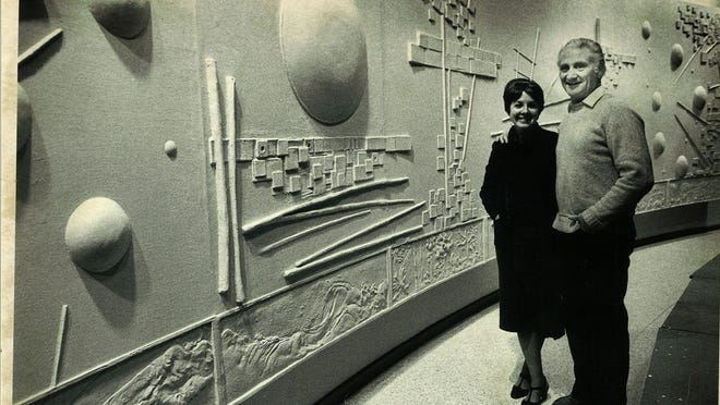 """Nancy and Mel Leiserowitz stand in front of their """"Wall of Creation"""" relief in the Molly Grove Chapel of Lansing's First Presbyterian Church."""